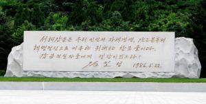 141204 - Naenara - Das Westmeerschleusensystem - 02 - Gedenkstein aus Granit, in den ein Ausspruch des Präsidenten KIM IL SUNG mit seinem persönlichen Schriftzug eingemeißelt ist